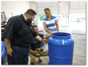 Conservation District Watershed Specialist, Jared Zinn, assists workshop participants determine an ideal location for the overflow of their rain barrel. Photo provided by Greene County Conservation District.