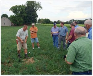 District Conservationist Andy Gaver digs into a hay field and discusses what healthy soil should look and feel like. Photo submitted by Beaver County Conservation District.