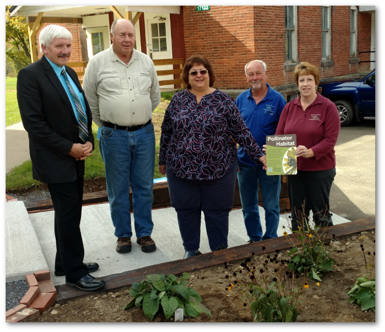 McKean County Conservation District (MCCD) directors and staff show Shambaugh the native plant and pollinator garden adjacent to their office building. The garden was funded by a Lumber Heritage Region grant. http://www.lumberheritage.org/grants1.htm    Pictured from left to right are: Cliff Lane, County Commissioner and MCCD Board Director; Kerry Fetter, MCCD Board Chairman; Brenda Shambaugh, PACD Executive Director; Bob Wright, MCCD Board Director; and Sandy Thompson, MCCD District Manager.